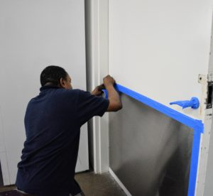 Everyone is busy preparing for our big launch. Here's Lincoln prepping a door for a new coat of paint.