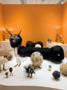 This is one installation view of The Haas Brothers' Ferngully exhibit. The twin artists hoped to capture a sense of childlike wonder with this display. It features animal sculptures in various shapes and colors - creatures made from Icelandic sheepskin with oversize heads and bronze legs.