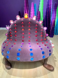 Here's a furniture piece called New Jersey Turnspike (2018), made from velvet, walnut wood, blown glass, electric wiring and light bulbs. This seat measures 60-inches by 50-inches by 50-inches.