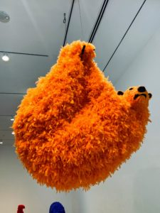 This is titled I Am Vitamin C (2018), and made with urethane foam, plastic and orange colored feathers.