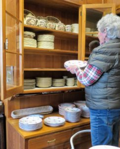 Here, Cheryl begins to put the plates back into the cabinet. It's a good idea to also take quick snapshots of how the plates and platters were positioned on the shelves before they were removed, so you know exactly how to put them back.