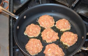 The meatballs are formed and placed into a large skillet.