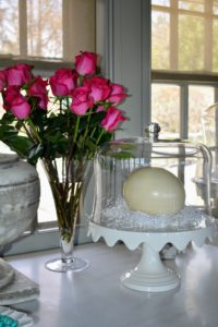 """Under this dome, a giant ostrich egg nesting on some white Easter basket """"nesting"""" filler. It looks so pretty next to my bouquet of pink roses."""