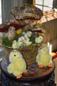 A whimsical woodland scene of chicks and toadstools sit atop this small table.