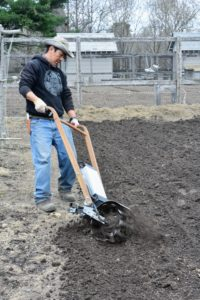 Here's Dawa tilling the soil in a patch where the boxwood will be planted.