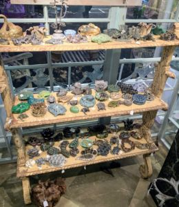Here is a table filled with all kinds of flower frogs. Flower frogs are made of lead, pottery, glass, or bronze and sit at the bottom of a bowl or a vase to hold flower arrangements firmly in place.