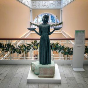 "Telfair Museums is also home to Sylvia Shaw Judson's famous Savannah Bird Girl statue. It's cast in bronze and stands 50-inches tall and shows a young girl wearing a simple dress and a contemplative expression, holding up two bowls, or ""bird feeders"". The statue became famous when it was featured on the cover of the non-fiction novel ""Midnight in the Garden of Good and Evil"" by John Berendt."