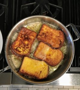 Here is the French toast coated and sizzling in the skillet with four tablespoons oil and two tablespoons butter. They are cooked until golden brown on both sides - about five minutes per batch, flipping only once.