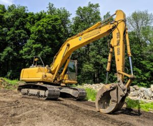 """Here is the excavator, which will pick up the material using the large """"jaws grab"""" bucket attachment and drop it into the tub grinder."""