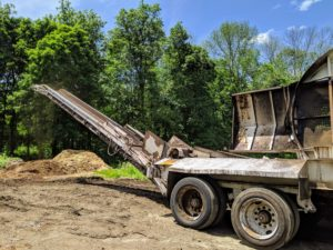 A continuous discharge conveyor carries the material away from the machine and piles it up in a mound.