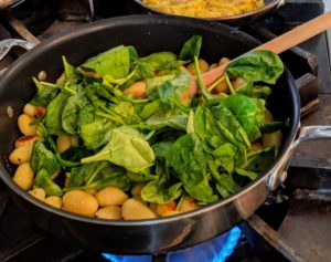 The spinach and half the basil leaves are now added to the pan with the butter and cooked until the spinach is wilted.