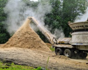 As the tub spins, friction actually causes some of the wood to smoke. Everyone wears masks and appropriate eye gear for protection near the machinery.