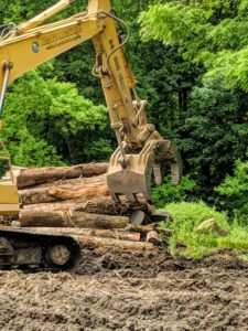 Dan begins operating the excavator and grabbing large amounts of logs and brush.