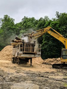 """Once Dan has the bucket over the grinder, he opens the """"jaws grab"""" and releases the debris into the hammermill at the bottom of the tub. As the tub revolves, the hammermill shatters the wood into smaller fragments."""