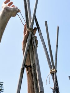 Gavin wraps the twine around the bamboo several times and makes sure it is taut enough to support the teepee structure.
