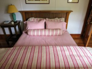 And here is the bed all dressed in cheerful pink, red and cream bedding.
