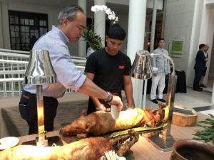 "Lechon, or roasted suckling pig, is one of the most celebrated dishes in the Philippines. Here, Chef Joel Binamira, the man behind the respected food blog ""Market Manila"" and the founder of Zubuchon, cuts through the crispy skin of the lechon with a plate. I tried several different types of lechon during my stay - all very good."