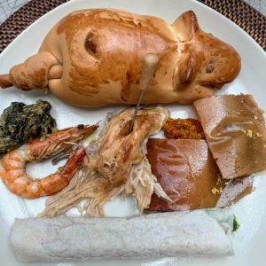 "Here is my plate with ""a little bite of everything"" plus a charming roll shaped like a pig. We were well-fed here in the Philippines."