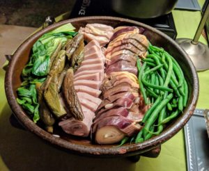 Fresh vegetables and sliced pork were displayed on this platter.