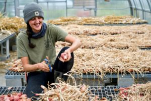 Assistant farm manager Lauren Cote cleaning shallots for the farmstand during the farm tours.