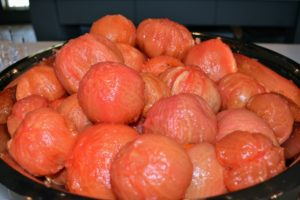 Once the tomatoes are peeled and hulled, they're dropped into another big, stainless steel bowl.