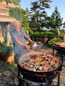 My friend, Chef Pierre Schaedelin of PS Tailored Events, cooked paella. Paella requires attentive care. Here he is adding more ingredients before stirring. This 36-inch pan is perfect for feeding this large group, and the round grill ensures even heating during the cooking process.