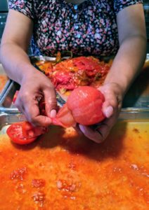 Sanu takes each tomato and hand peels the skins – look how easy this is to do – boiling them really helps.