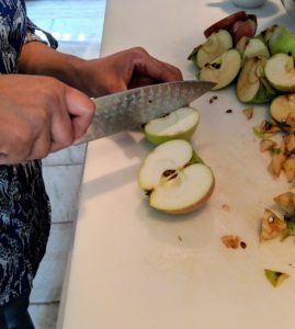 Sanu cuts each apple in half, and double-checks there are no seeds. This is important because seeds are tannic and cooking with them will impart a bitter taste.