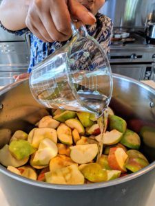 Sanu pours the water over all the apples.