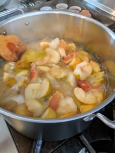 Occasionally, Sanu stirs the apples with a wooden spoon to prevent burning. Within minutes, they start to soften.