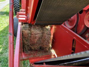 Once done, the bale comes out the back of the baler. Each bale is about 15 by 18 by 40 inches large. The bales are usually wrapped with two pieces of twine and are light enough for one person to handle, about 45 to 60 pounds each.