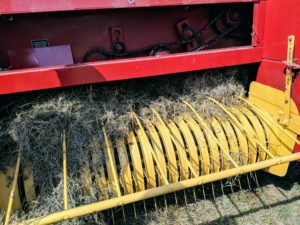 Here is a closer look at the baler's mechanisms. A measuring device—normally a spiked wheel that is turned by the emerging bales—measures the amount of material that is being compressed and then knotters wrap the twine around the bale and tie it off.