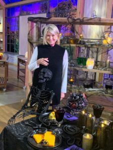 Here I am with one of my favorite Halloween pieces - my 5-foot tall posable skeleton. It comes in black and in silver. They're great indoors at a desk, in a chair, or hung in the doorway. Use them outdoors on a stone wall, or sitting on the front porch - all your trick-or-treaters will love them.