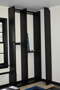 Shelving uprights are installed on the other side of the room.