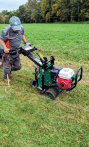 This sod cutter weighs about 380-pounds. It cuts 12-inch widths of sod and can cut more than 100-feet per minute. This ground is quite dry and tough, so it takes a bit longer to cut through. Chhiring pushes the cutter forward following the lines and periodically checking to see his cuts.
