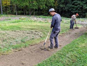Chhiring and Phurba rake up any sod remnants in the bed.