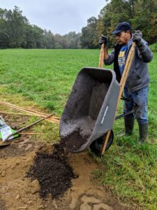 Carlos drops some nutrient-rich compost near every hole - compost we make right here at my farm.