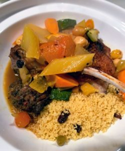 The Couscous Royale is plated with vegetables, and a piece each of lamb, chicken and then sausage, and placed into the base section of the tagines.