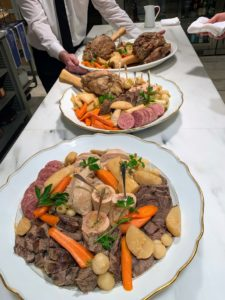 Here is the pot-au-feu. All the cooked meats and vegetables are arranged on serving platters. Some of the meat is carved off ahead of the buffet service.