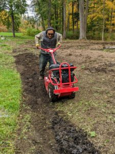 As he moves, Pete makes sure to overlap his passes slightly, so every bit of soil is covered. Tilling also helps to level the ground as it turns over the soil.
