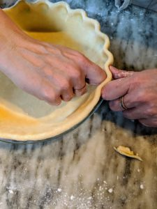 Crimping is not only decorative, but it makes it less likely the sides of the pie will fall or shrink during baking. Molly crimps the dough all the way around.