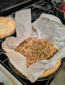 When the crust is ready to blind bake, line the crust with parchment paper, and fill it with pie weights. Bake it for 20-minutes and then remove the parchment and weights. Then bake it until the crust is dry but not brown, about five minutes more.