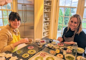 "And down at my Maple Avenue House, Jessie Damuck and Molly Wenk are making wreath cookies from my latest book, ""Cookie perfection. These wreath cookies are covered with lemon glaze and then embellished with nuts, dragees, and candied ginger."