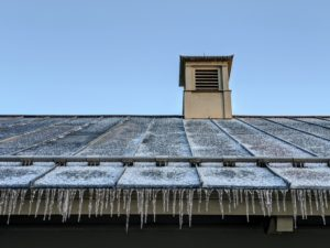 Icicles form when ice or snow is melted by the sunlight and then refreezes as it drips. During ice storms, icicles also form when rain slightly below freezing accumulates. Over time, water runoff causes the icicles to grow. These icicles are on the overhang of my carport.