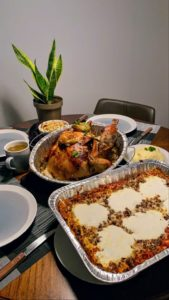 """Graphic designer, Mario Silva, shows his Thanksgiving table. """"We cooked a turkey, lasagna, mashed potatoes, and salad - everything from scratch. I was with my boyfriend, Naqi, and our friend Pedro, at our apartment in Astoria, Queens, New York."""""""