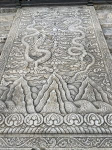 "This is the central staircase in the outer courtyard. It could only be used by the Emperor. The center is a slab of 250 tons of stone engraved with beautiful dragons. This fresco is called ""Dragons floating among the clouds""."
