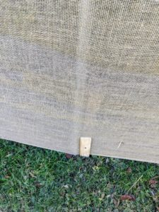 It looks very tidy once attached. Both the metal and wood stakes can be seen through the fabric.
