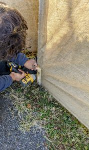 To make it taut, the burlap is pulled down and attached to the ground stakes using the strips and screws.
