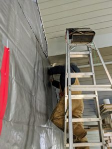 Meanwhile, I decided we needed to create a dust barrier between the hay side and this storage side of the loft. I instructed the crew to create a wall using industrial size tarps. Here's Chhiring securing the tarps to the ceiling and to the sidewall surfaces.