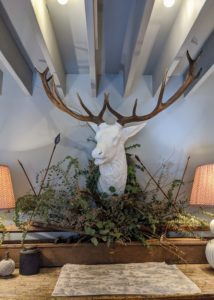 "And behind the counter, this beautiful stone buck head decorated with foliage and arrows - the antlers fit perfectly in between the beams of the ceiling. The next time you're in this area, please stop by ""The Huntress"" - you will find it a treasure trove of beautiful and distinctive gifts and accessories."